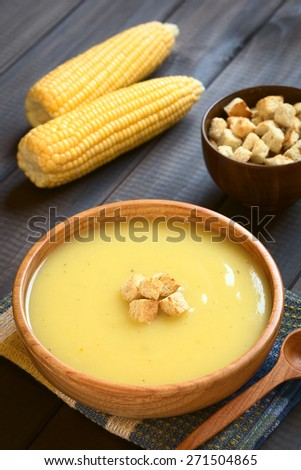Cream of corn soup in wooden bowl with croutons on top, photographed on dark wood with natural light (Selective Focus, Focus on the front of the croutons on the soup) - stock photo