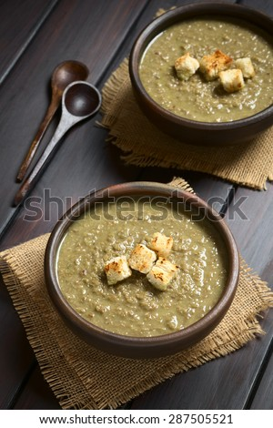 Cream of lentil soup in rustic bowls with croutons on top, wooden spoons on the side, photographed on dark wood with natural light (Selective Focus, Focus on the front of the croutons on first soup) - stock photo