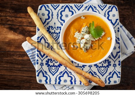 Cream of pumpkin soup with blue cheese and homemade grissini bread sticks in a white bowl on a wooden dark background. selective Focus - stock photo