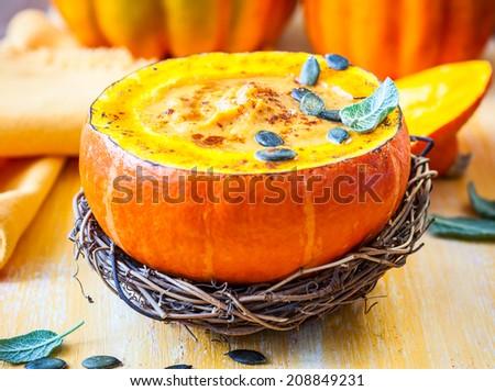 Cream of pumpkin soup with pumpkin seeds and sage  in pumpkin.Selective focus - stock photo