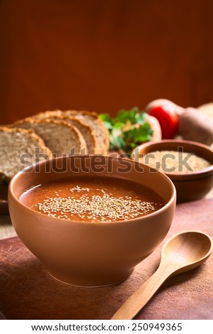 Cream of vegetable soup made of tomato, carrot, potato and parsley served in bowl and sprinkled with sesame seeds, photographed with natural light (Selective Focus, Focus in the middle of the soup) - stock photo