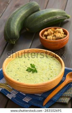 Cream of zucchini soup in wooden bowl garnished with parsley leaf, croutons in the back, photographed with natural light (Selective Focus, Focus on the parsley leaf) - stock photo