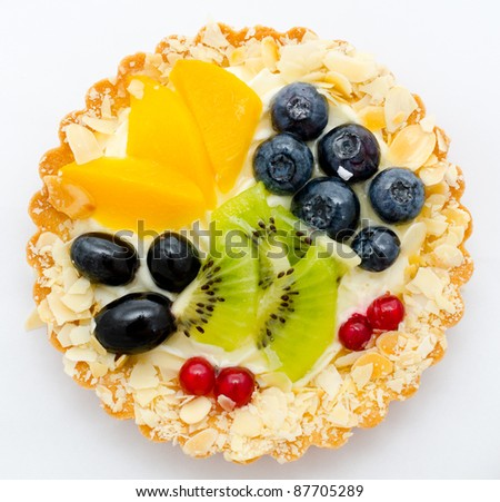 cream on a tartlet served with peach, kiwi and berries - stock photo