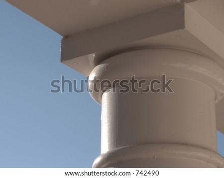 Cream painted stone column against blue sky