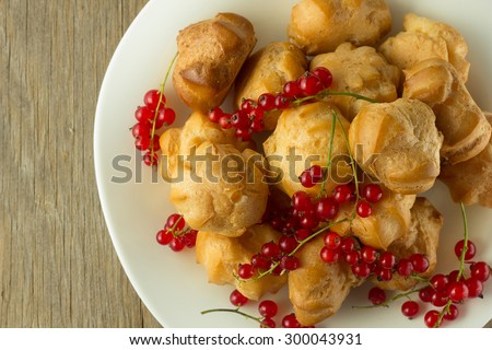 Cream puffs and red currant on white plate selective focus horizontal top view - stock photo