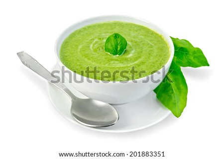 Cream soup green from spinach in a white bowl with leaf spinach on a plate, spinach leaves isolated on white background - stock photo