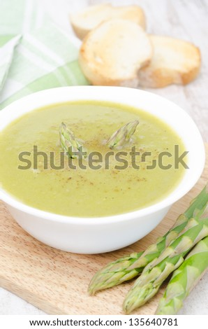 cream soup of asparagus and green peas in a white bowl with toasted bread