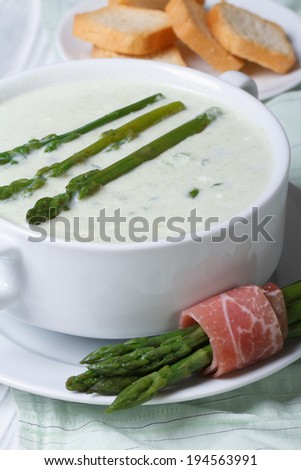 Cream soup of asparagus close-up in white plate and croutons. vertical  - stock photo