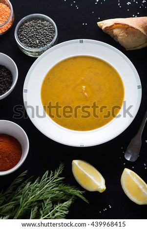Cream soup of assorted lentil. Yellow and green lens, spices as raw for meal and lemon on black backgraund. Healthy, appetizing, delicious, vegetarian food. Top view, copy space. - stock photo