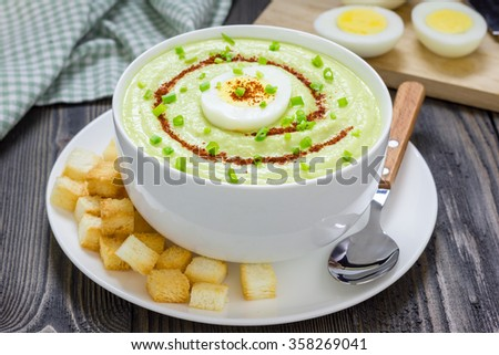 Cream soup with avocado, garnished with egg and croutons. Healthy eating. - stock photo