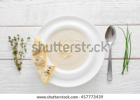 Cream-soup with cheese and bruschetta on white wooden background. Restaurant serving of vegetarian soup-puree with bread and spoon, flat lay - stock photo