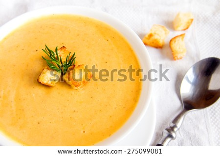 Cream soup with croutons and dill  on white napkin, horizontal close up - stock photo