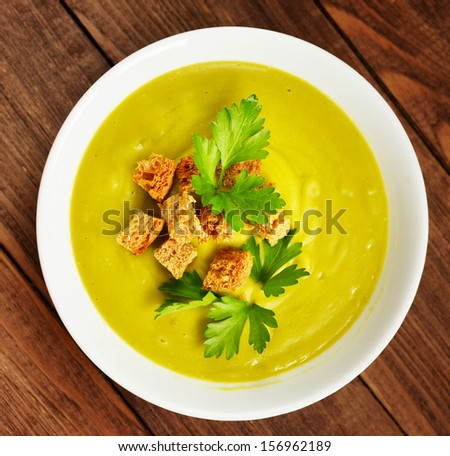 cream soup with dried crusts and green parsley - stock photo