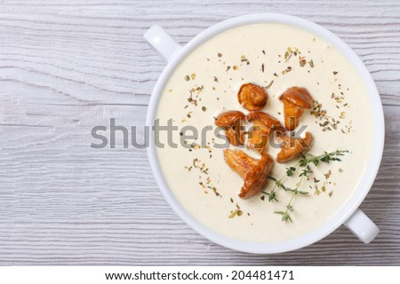 cream soup with mushrooms chanterelles and herbs on a wooden background horizontal top view  - stock photo