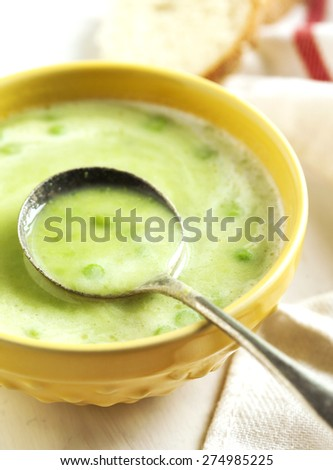 Cream soup with potato and green peas. Selective focus