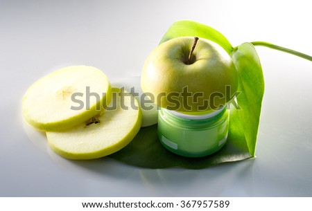 Cream with an apple, a flower on a green leaf