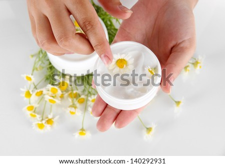 Cream with chamomile in hand isolated on white - stock photo