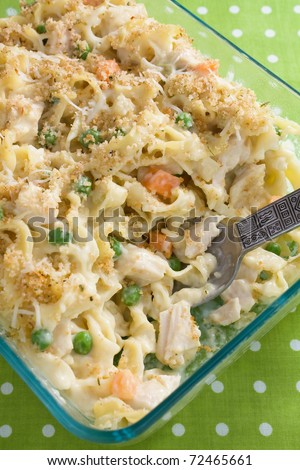 Creamy baked chicken noodle casserole with peas and carrots.