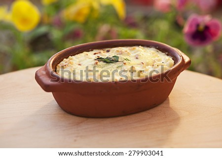 Creamy baked macaroni and cheese in a clay pot - stock photo