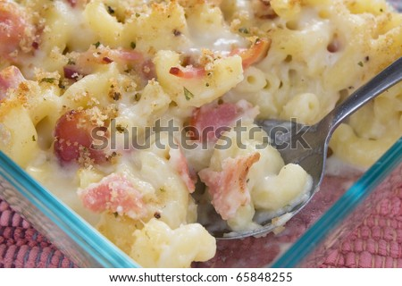 Creamy baked macaroni and cheese with bacon, provolone cheese, and mozzarella cheese, then topped with bread crumbs. - stock photo