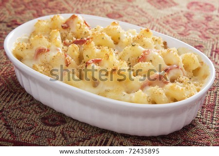 Creamy baked macaroni and cheese with sun-dried tomatoes, provolone cheese, and mozzarella cheese, then topped with bread crumbs. - stock photo