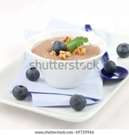 creamy caramel pudding in bowl with bilberries