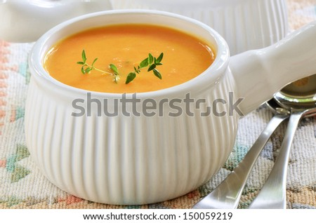 Creamy carrot and sweet potato soup with sprig of thyme in white ribbed soup bowl - stock photo