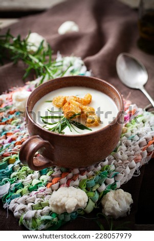 Creamy cauliflower soup with herbs and croutons - stock photo