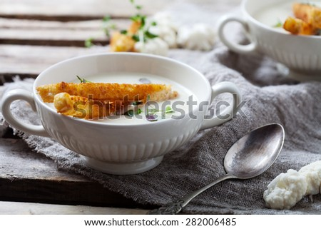 Creamy cauliflower soup with toasted bread - stock photo