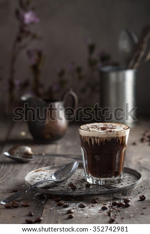 Creamy coffee with liquid chocolate in a glass - stock photo