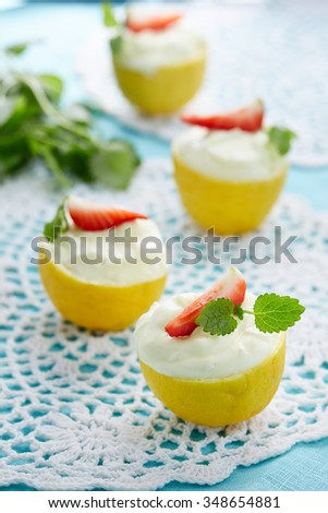 creamy dessert served in lemon halves decorated with strawberry slice and mint leaves - stock photo