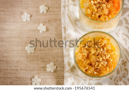 creamy dessert with caramelized pears and nuts in the glass. toning. selective focus on pear in lower glass - stock photo