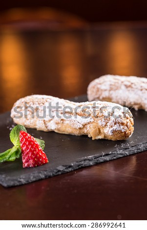 Creamy eclair dessert with strawberry on stone plate on wooden table - stock photo