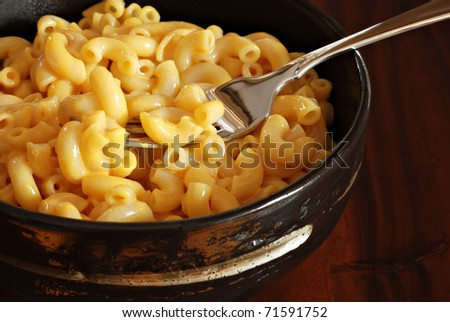 Creamy macaroni and cheese in stoneware bowl on wood background.  Macro with shallow dof.  Focus on fork. - stock photo