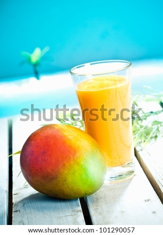 Creamy mango smoothie with blended fresh mango juice and yoghurt served overlooking a tropical ocean