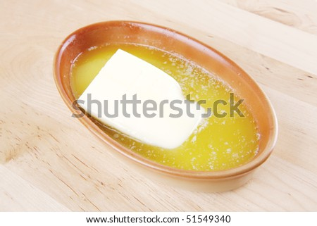 creamy melted butter in bowl on wooden plate - stock photo