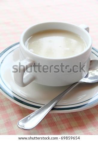 Creamy mushroom soup served on white bowl with silver spoon - stock photo