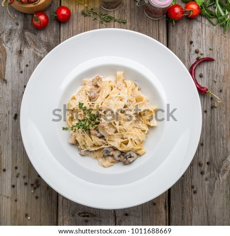 Creamy mushroom spinach pasta. toning. selective focus, on a wooden table