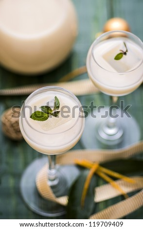 Creamy orange liqueur with Christmas decoration - stock photo
