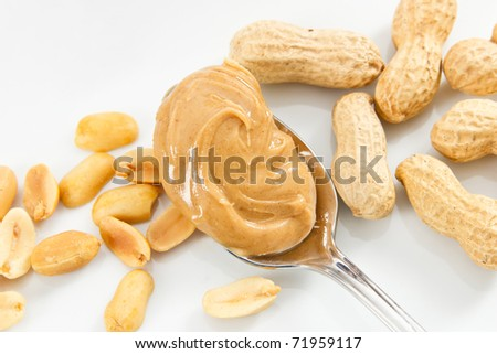 Creamy peanut butter and peanuts against a white tray show healthy foods that are also allergens - stock photo