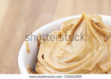 Creamy peanut butter in a dish with shallow depth of field.