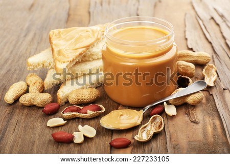 Creamy peanut butter in jar, on wooden table - stock photo