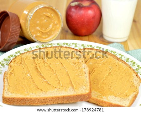 Creamy peanut butter on whole wheat bread on a plate - stock photo