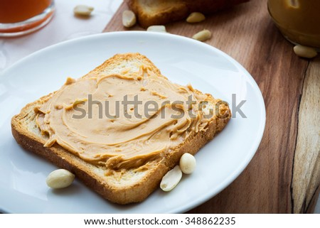 Creamy peanut butter sandwich or toast on wooden background, selective focus, close up. Rich breakfast.