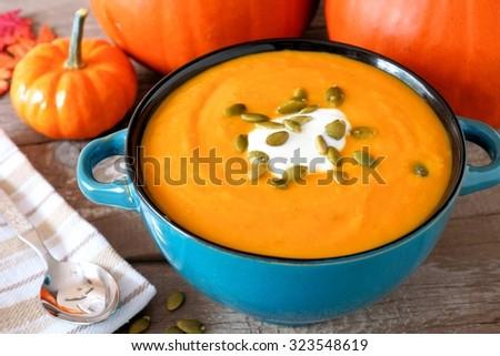 Creamy pumpkin soup topped with pumpkin seeds and cream in a blue bowl close up - stock photo