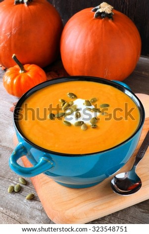 Creamy pumpkin soup topped with seeds and cream in a blue bowl with autumn pumpkins in background - stock photo