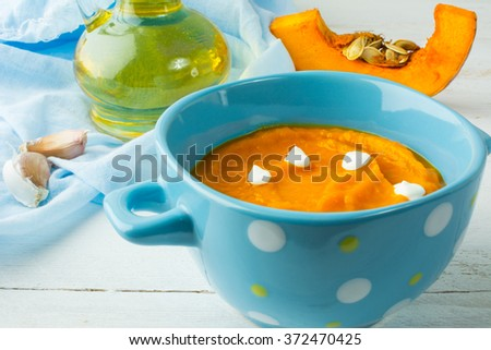 Creamy pumpkin squash vegetable soup with cream in a blue bowl on white wooden background. Pumpkin soup. Squash soup. Soup. Creamy soup. Vegetable soup  - stock photo