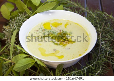 Creamy soup, made of wild organic asparagus, decorated with fresh laurel and rosemary and Mediterranean virgin olive oil, served on wooden table-selective focus - stock photo