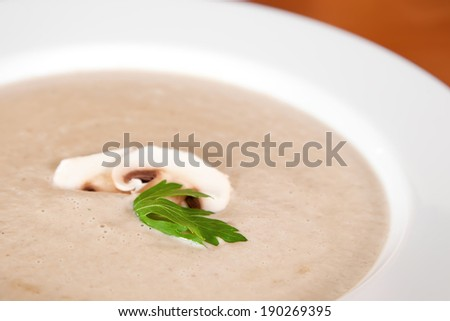 Creamy soup with champignon mushrooms and parsley