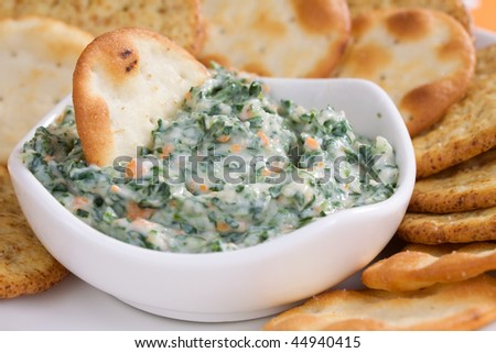 Creamy spinach dip with crackers. - stock photo